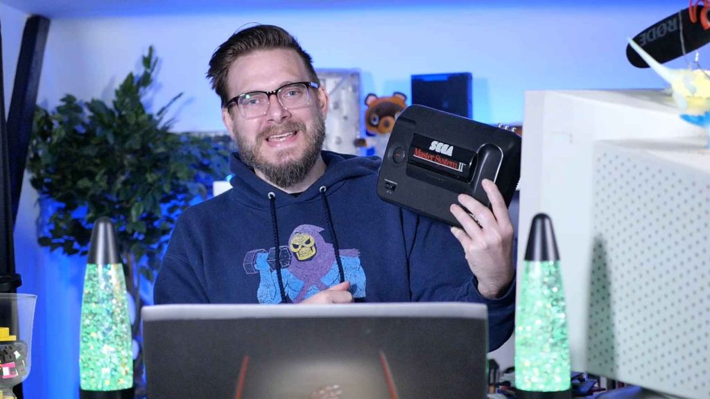 Nostalgia Nerd with a Sega Master System, looking happy about it