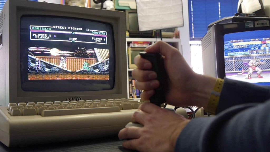 Joystick, with monitor behind, showing the horror of Street Fighter II on the Commodore 64